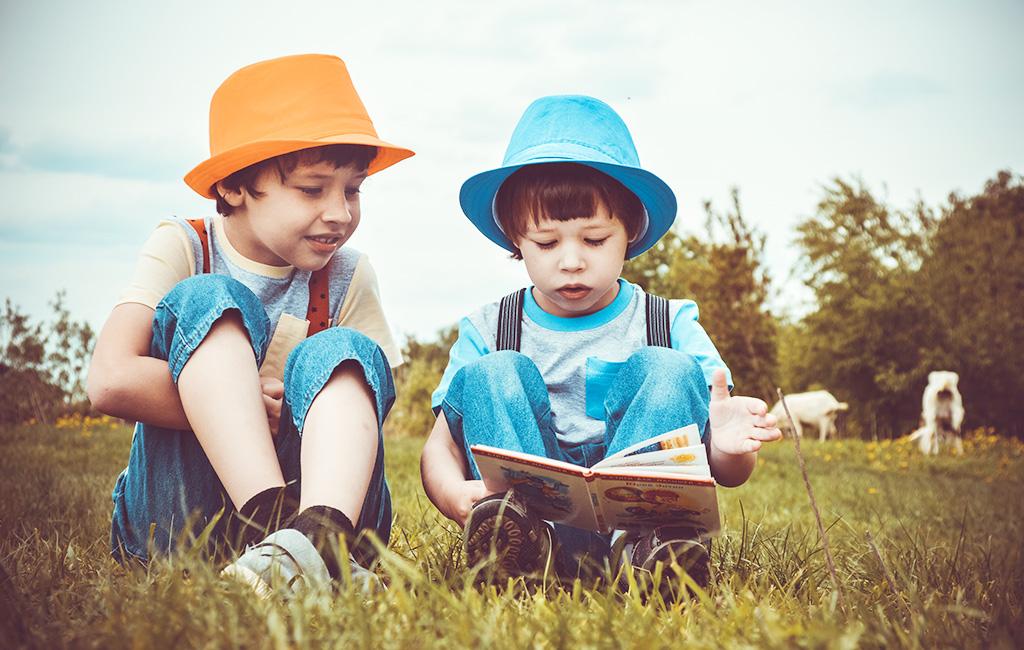 Children Read In A Field