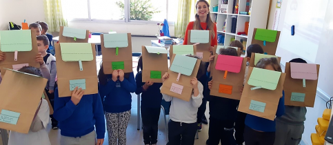 Students of the Kindergarten of mandoulides schools with their faces covered by paper bags and with their teacher on the back