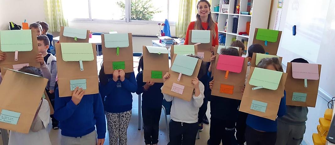 Ομάδα μαθητών του νηπιαγωγείου των Εκπαιδευτηρίων Μαντουλίδη με τη δασκάλα τους,, που κρατάνε μπορστά στα πρόσωπα τους φακέλους με διάφορα χρώματα