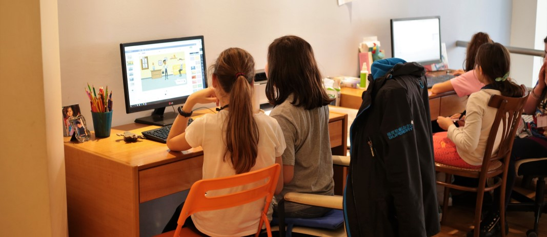 4 students of the 5th grade of mandoulides schools , looking at computer screens while getting informed about the dangers on the Internet