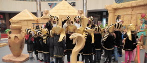 The students of the kindergarten of mandoulides schools , wearing pharaoh hats and looking and listening to their teachers talking to them about ancient egypt