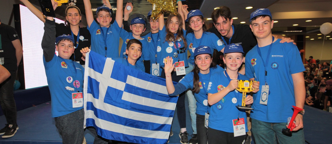 The members of M-RAST team of mandoulides schools with ,dressed in blue, holding the Greek flag and the two cups they won, together with their teachers and coaches