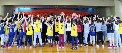 Students of the 6th and 7th grade of mandoulides schools looking at the crowd with their hands up, after the basketball game between them
