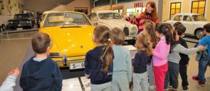 Μαθητές των beatles των εκπαιδευτηρίων μπροστά από ένα κύτρινο και ένα άσπρο αμαξι να ακούνε την περιγραφή της ξεναγού στο NOESIS