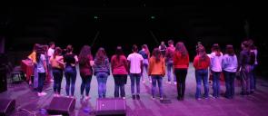 Μαθητές του λυκείου των εκαπιδευτηρίων με τις πλάτες γυρισμένες στη σκηνή της θεατρικής παράσταστης