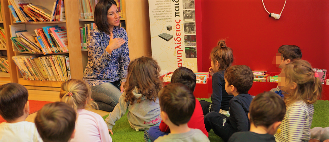 Students of the kindergarten of mandoulides schools sitting and listening to teacher at Daniilideios Children's Library