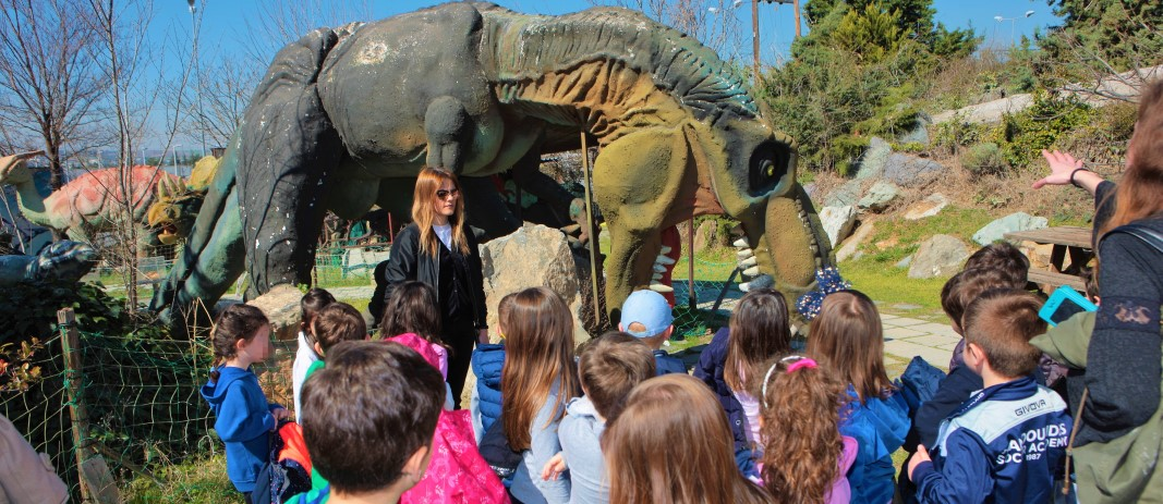 Students of the kindergarten of mandoulides schools looking at a T-Rex reproduction during their visit to the dinosaur park