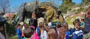 Τα νήπια των εκπαιδευτηρίων μαντουλίδη κοιτάζουν έναν τυρανόσαυρο ρεξ καθώς η ξεναγός τους εξηγεί λεπτομέρειες για τον δεινόσαυρο