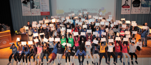 All the participating students of MAndoulides Schools on the stage holding their certificates up high