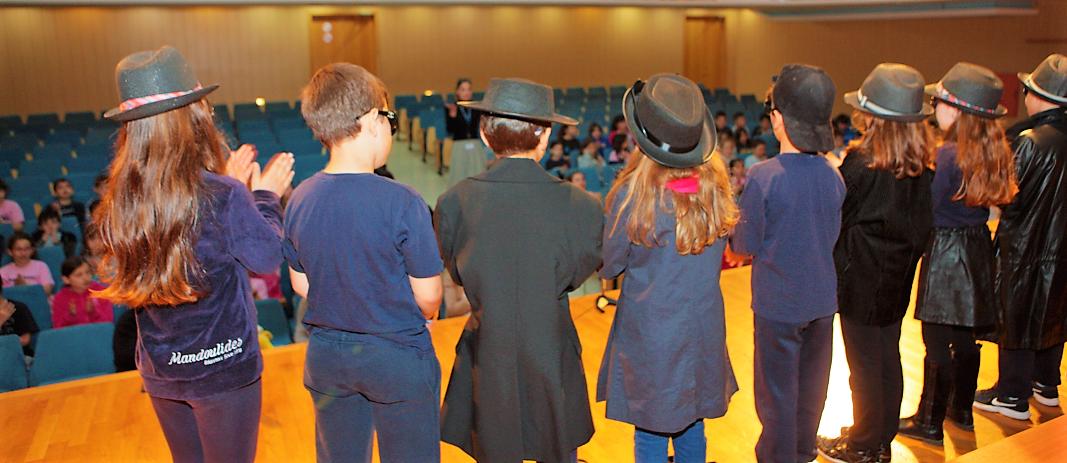 Μαθητές του δημοτικού των εκπαιδευτηρίων μαντουλίδη πάνω στη σκηνή του θεάτρου με τα πρόσωπα στραμένα στο κοινό