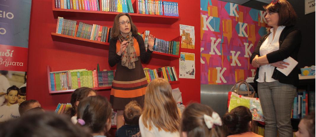 Η συγγραφές κ. Δημόκα μιλάει στους μαθητές του δημοτικού των εκπαιδευτηρίων Ε. Μαντουλίδη για το νέο βιβλίο της ενώ αυτοί είναι καθισμένοι στο πάτωμα και την παρακολουθούν