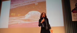Η κ. Δημότα στη σκηνή του θεάτρου των Εκπαιδευτηρίων, μιλάει κρατώντας ένα μικρόφωνο και πίσω της φαίνεται μια εικόνα με το εξώφυλλο του βιβλίου της