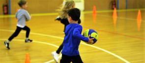 3 παιδιά του νηπιαγωγείου τρέχουν μέσα στο γήπεδο των εκπαιδευτηρίων