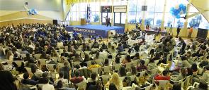 To αθλητικό κέντρο των εκπαιδευτηρίων γεμάτο με θεατές που παρακολουθούν στη σκηνή ένα ντουέτο