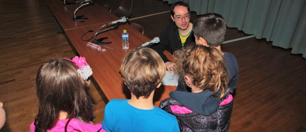 aris dimokidis sits on a wooden table and speaks to 4 students of mandoulides schools