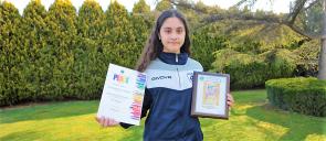 Η μαθήτρια των Εκπαιδευτηρίων Δήμητρα - Μελίνα Παπαποστόλη βραβεύτηκε για την κατάκτηση της 1ης θέσης σε διαγωνισμό ζωγραφικής αφίσας κρατάει τα δύο βραβεία της όρθια με δένδρα πίσω της
