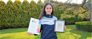 student D. - M. Papapostoli dressed in blue, holding the award she won, with green and trees behind her