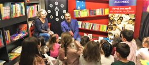 Aris Dimokidis talks to the little students of mandoulides schools about his new book and the students sit down on the floor looking at him