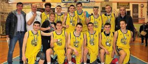The boys of mandoulides basketball team wearign their yellow shirts, hugged with each other, 6 of them standing and 6 of them sitting, with their coaches near them