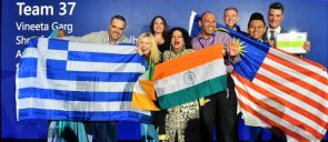 Mr Komianos, holding the greek flag along with his teammates and the other flags, smiling