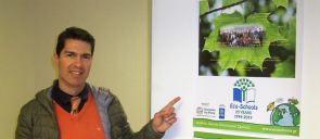 Mr Sarantidis points his finger on the green flag award banner