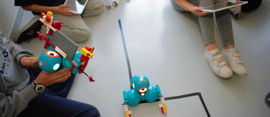 Ένα μπλέ ρομποτάκι στο κέντρο της εικόνας και τα παιδιά με tablets γύρω του