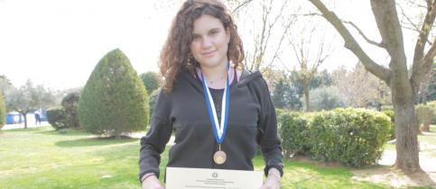 Η μαθήτρια των Εκπαιδευτηρίων Χ. Πατσιά στέκεται όρθια με φόντο πράσσινο γρασίδι και φυτά, φορόντας το μετάλλιο της και κρατώντας το δίπλωμα που κέρδισε