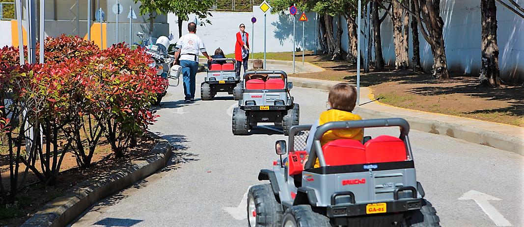 τρία παδικά αυτοκίνητα με οδηγούς τους μαθητές των beatles των εκπαιδευτηρίων, που κινούνται σε έναν δρόμο ενώ δύο δάσκαλοι τους καθοδηγούν