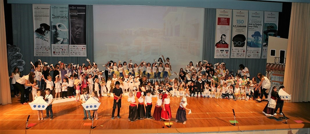 Στην Αποχαιρετιστήρια Γιορτή English Garden «Children of the World», οι μικροί μαθητές των εκπαιδευτηρίων βρίσκονται απλωμένοι στη σκηνή του κέντρου εκδηλώσεων με τα χέρια σηκωμένα ψηλά
