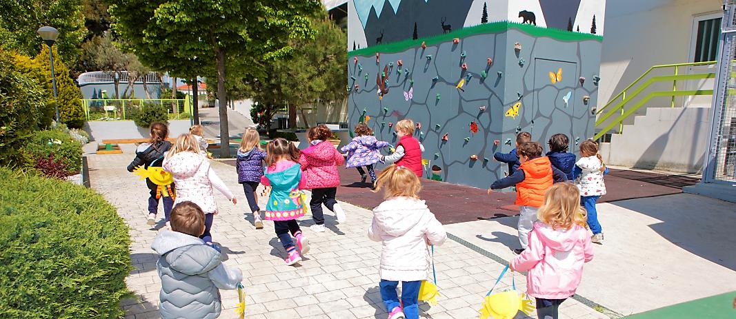Οι μαθητές των English garden των εκπαιδευτηρίων τρέχουν στο προαύλιο δίπλα στον τοίχο αναρίχησης