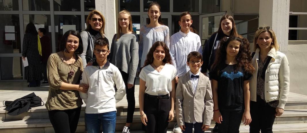 Οι 8 μαθητές των Εκπαιδευτηρίων, 5 κορίτσια και 3 αγόρια μαζί με τις 3 δασκάλες τους, στέκονται όρθιοι στα σκαλιά της εισόδου και χαμογελάνε