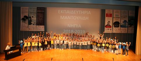 Οι μαθητές του νηπιαγωγείου των εκπαιδευτηρίων συγκεντρωμένοι στη σκηνή του κέντρου εκδηλώσεων, σηκώνουν τα χέρια τους ψηλά