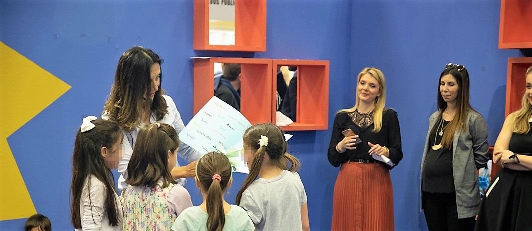 H συγγραφέας Τασούλα Τσιλιμένη δείχνει το βιβλίο της σε 3 μαθήτριες του δημοτικού των εκπαιδευτηρίων