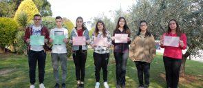Οι 7 μαθητές των Εκπαιδευτηρίων που διακρίθηκαν, 2 αγόρια και 5 κορίτσια, στέκονται στο γρασίδι και χαμογελούν κρατώντας τους επαίνους που κέρδισαν