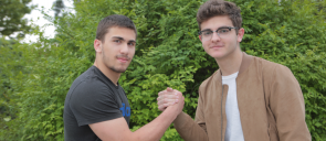 Οι μαθητές του λυκείου των εκπαιδευτηρίων, Μάστορης και Πλοιαρίδης ενώνουν με χειραψία τα χέρια τους , με φόντο το πράσινο της αυλής των εκπαιδευτηρίων
