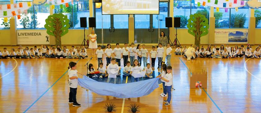 Οι μαθητές της Α΄ Δημοτικού των Εκπαιδευτηρίων απλωμένοι στο γήπεδο μπάσκετ των εκπαιδευτηρίων, στο κέντρο μία ομάδα μαθητών να κρατούν απλώμενο ένα γαλάζιο σεντόνι