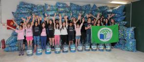Οι μαθητές του Δημοτικού και του Γυμνασίου-Λυκείου των Εκπαιδευτηρίων με σηκωμένα τα χέρια ψηλά, μπροστά από τσουβάλια γεμάτα με πλαστικά καπάκια