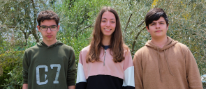 Οι 3 μαθητές των εκπαιδευτηρίων που που πέρασαν στον Πανελλήνιο Τελικό του Παγκοσμίου Πρωταθλήματος της Microsoft , 2 αγόρια και ανάμεσα τους ένα κορίτσι, χαμογελούν με πράσινο φόντο