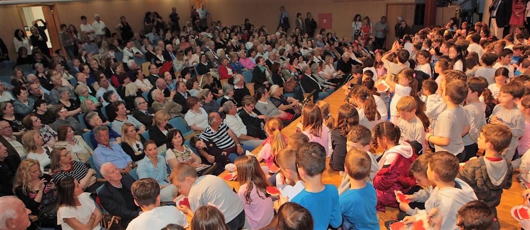 Οι μαθητές του δημοτικού των εκπαιδευτηρίων καθισμένοι πάνω στη σκηνή του κέντρου εκδηλώσεων κοιτάζουν τους παπούδες και τις γιαγγιάδες τους που βρίσκονται μπροστά τους στις θέσεις των θεατών