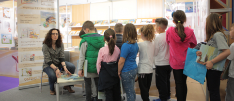 H συγγραφέας Εύη Τσιτιρίδου καθιστή χαμηλά, μιλάει με τους μαθητές του δημοτικού των εκπαιδευτηρίων που έχουν κάνει μια ουρά μπροστά της και περιμένουν τη σειρά τους