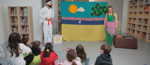A girl dressed in green and a man wearing a karate suit, perform in front of sitting kids
