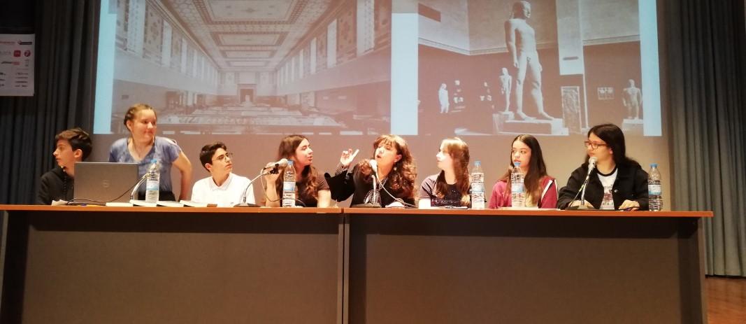 Η συγγραφέας Αγγελική Δαρλάση στην σκηνή του κέντρου εκδηλώσεων των εκπαιδευτηρίων με ένα γραφείο με 7 μαθητές, μιλάει με το κοινό για θέματα που τους απασχολούν
