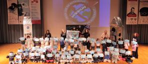 οι μαθητές και οι μαθήτριες των τάξεων Α΄- Δ' Δημοτικού που έλαβαν μέρος στο εκπαιδευτικό πρόγραμμα Mission X: Train Like An Astronaut συγκεντρωμένοι στη σκηνή του κέντρου εκδηλώσεων των εκπαιδευτηρίων με τις δασκάλες τους κρατώντας μπροστά στα πρόσωπα τους τους επαίνους που έλαβαν από το πρόγραμμα