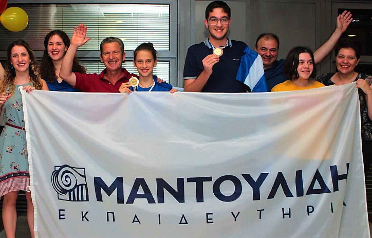 Η μαθητές Μ. Κωνσταντινίδου και Κ. Κωνσταντινίδης με το αργυρό και το χάλκινο μετάλλιο κρατώντας την Ελληνική σημαία