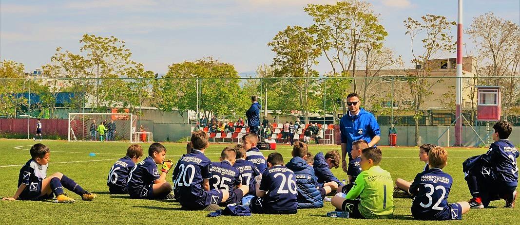 Στην Εκδρομή Ακαδημίας Ποδοσφαίρου στην Αθήνα, οι μικροί ποδοσφαιριστές των εκπαιδευτηρίων καθισμένοι στο γρασίδι του γηπέδου ποδοσφαίρου ακούν τον προπονητή τους
