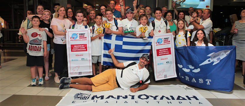 Τα μέλη της ομάδας M RAST των Εκπαιδευτηρίων μαζί με τους coach καθηγητές τους και γονείς, πανηγυρίζουν κρατόντας την ελληνική σημαία