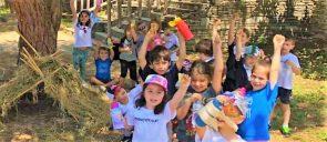 Οι μικροί μαθητές των beatles με τα χέρια σηκωμένα χαμογελούν σε ένα πράσσινο δάσος με δένδρα