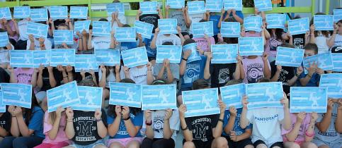 Οι μαθητές των τάξεων Α΄, Β΄, Γ΄ και Δ΄ Δημοτικού των Εκπαιδευτηρίων κρατούν μπρόστα στο πρόσωπο τους τους επαίνους που έλαβαν από το πρόγραμμα Mission X