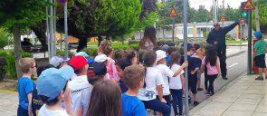 Τα Νήπια των Εκπαιδευτηρίων, με αφορμή τη θεματική ενότητα «Μαθαίνω να κυκλοφορώ με ασφάλεια», επισκέφθηκαν το Πάρκο Κυκλοφοριακής Αγωγής Καλαμαριάς στέκονται σε μια γραμμή όπου ένας κύριος τους δείχνει ένα φανάρι