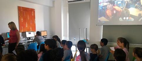 Οι μαθητές της Δ΄ Δημοτικού - Bilingual των Εκπαιδευτηρίων με τη δασκάλα τους κοιτούν και μιλούν με έναν μαθητή
